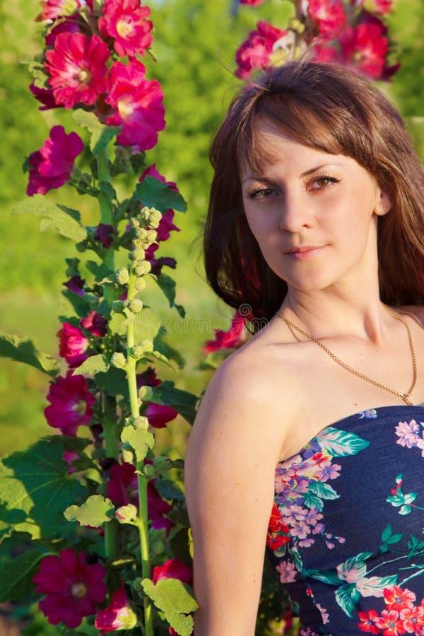 Stående av flickan på naturen i blommor arkivfoton