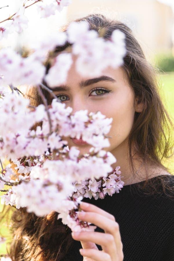 Stående av flickan som döljer bak att blomma filialen royaltyfria bilder