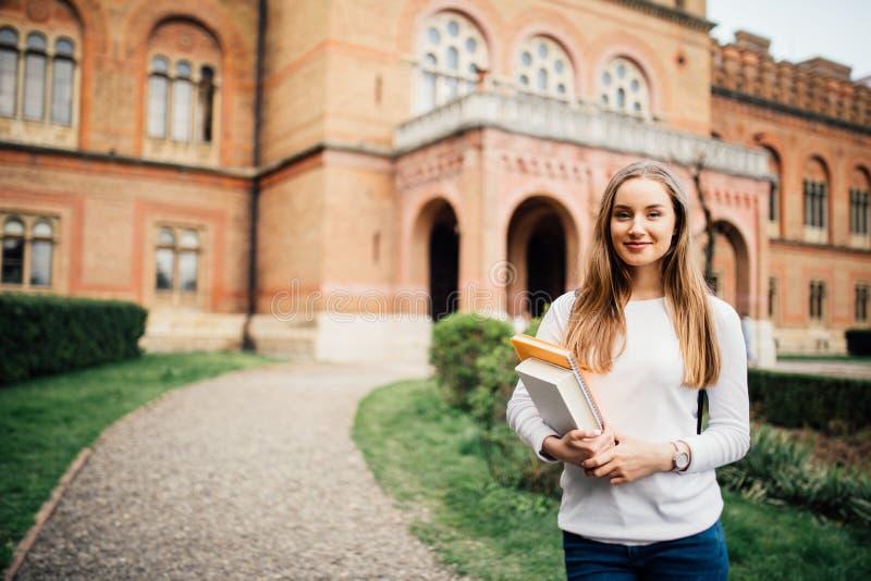 Stående av flickauniversitetsstudenten utomhus på universitetsområde fotografering för bildbyråer