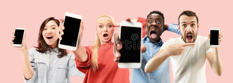 Stående av folk som visar skärmen av mobiltelefonen som isoleras över korallbakgrund arkivfoto