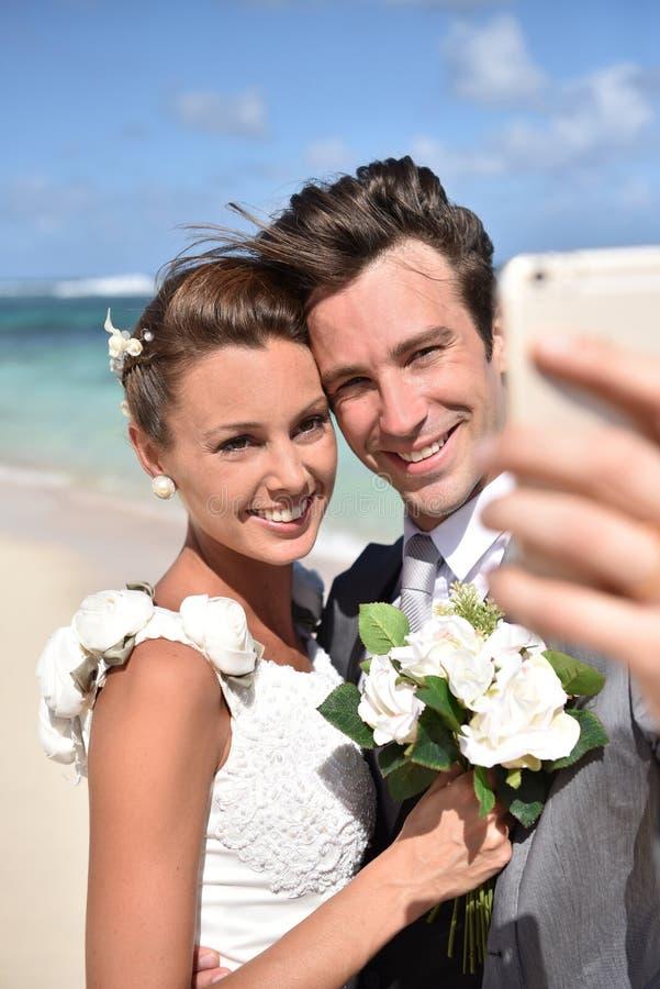 Stående av fresly gifta paret på stranden royaltyfri bild