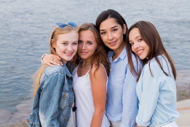 Stående av fyra femlevänner som ser vänliga på kameran, leende som är lyckligt folk livsstil, kamratskap royaltyfria bilder
