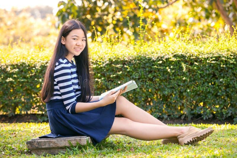 Stående av gamla asiatiska tonåriga tolv år och skolbok i hand arkivbild