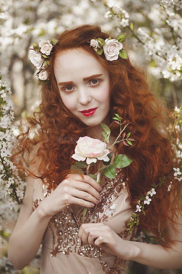 Stående av Gentle kvinnan med långt rött hår med en ros i en blommande trädgård Rödhårig flicka med blek hud och blått arkivbild
