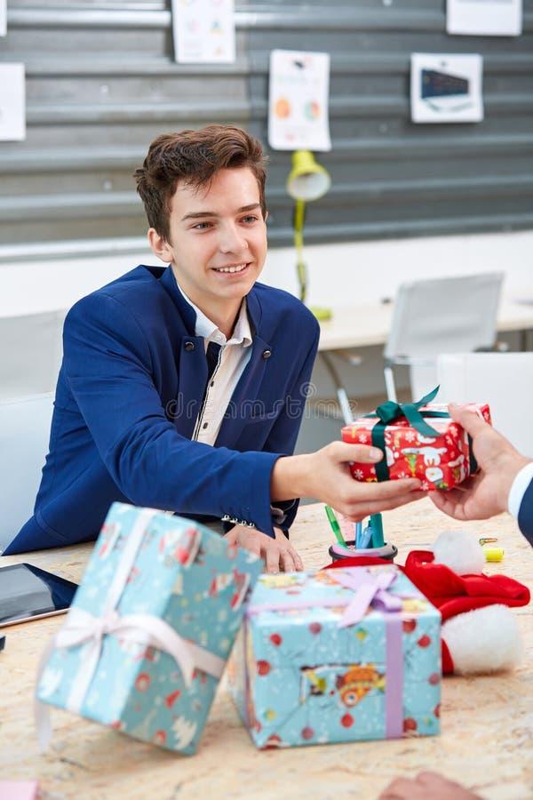 Stående av glade kollegor som till varandra ger xmas-gåvor Den lyckliga mannen tycker om på ferier på havet arkivbilder