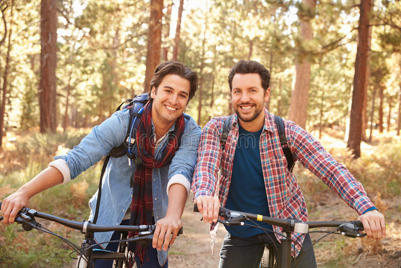 Stående av glade manliga par som cyklar till och med nedgångskogsmark fotografering för bildbyråer