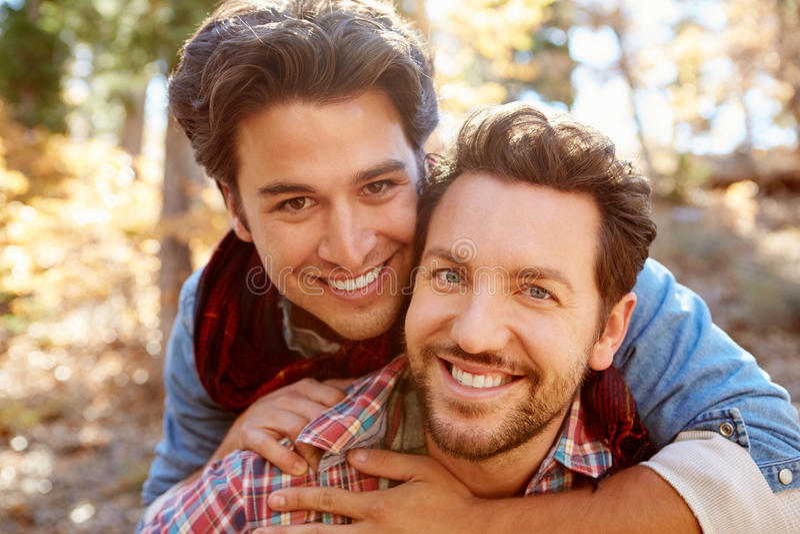 Stående av glade manliga par som går till och med nedgångskogsmark arkivbild