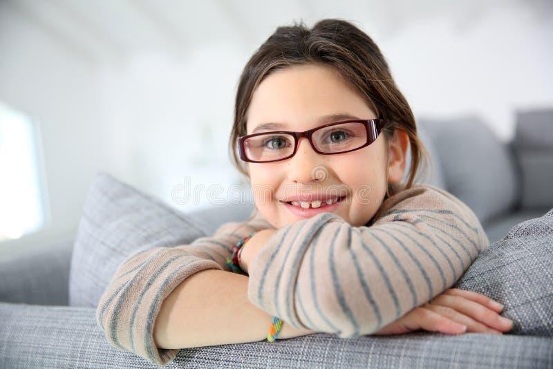 Stående av gladlynt flickasammanträde på soffan royaltyfri foto