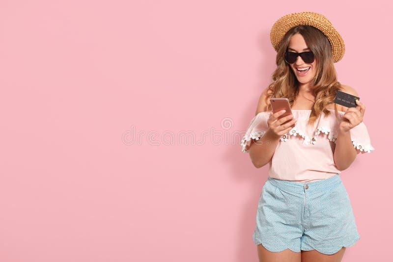 Stående av gladlynt lyckligt bärande sommarljus för ung kvinna - rosa blus, blåa kortslutningar, svart glasögon och innehav för s royaltyfri bild