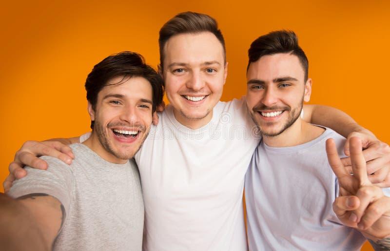 Stående av gladlynta grabbar som gör selfie och att ha gyckel royaltyfri foto