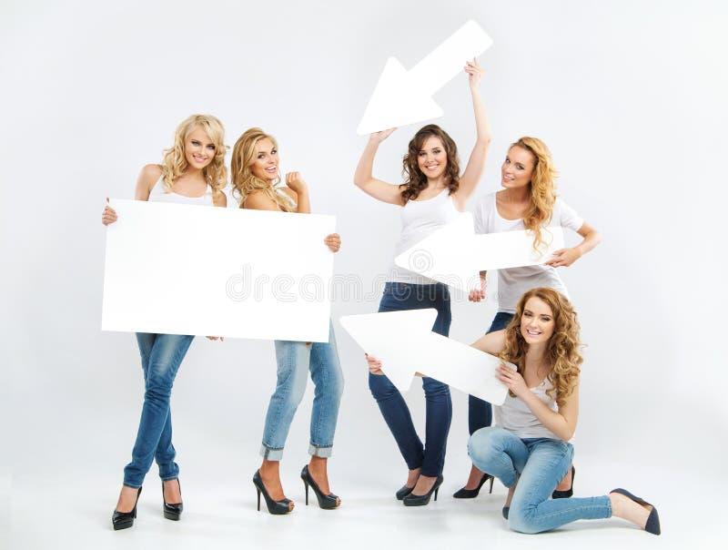 Stående av gladlynta unga damer med pilar royaltyfri foto