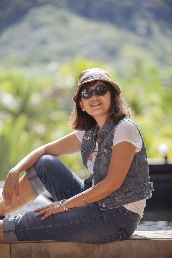 Stående av glas för hatt och för sol för sugrör för asiatisk 40-talårskvinna bärande royaltyfri bild