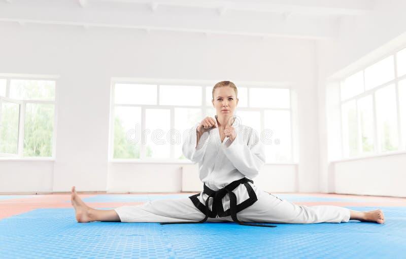 Stående av graden för svart bälte för karateflicka som sträcker henne ben för hård utbildning royaltyfria foton