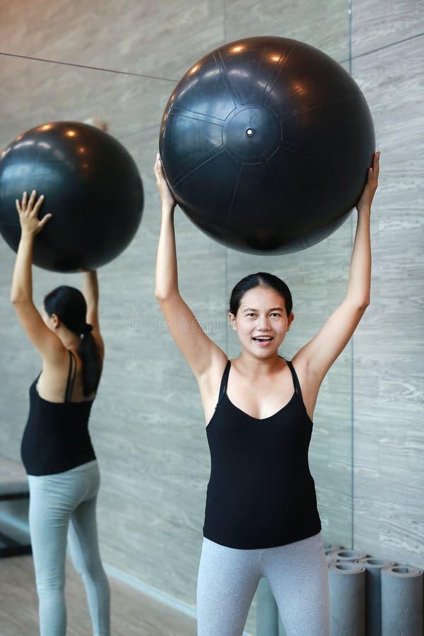 Stående av gravida kvinnan som övar med fitball på sportkorridoren arkivbilder