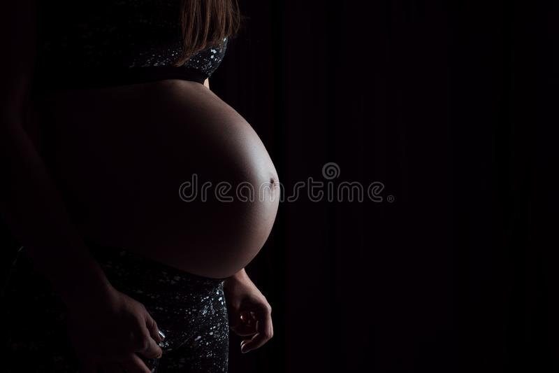 Stående av gravida kvinnan som trycker på hennes buk på svart backgroun royaltyfri bild