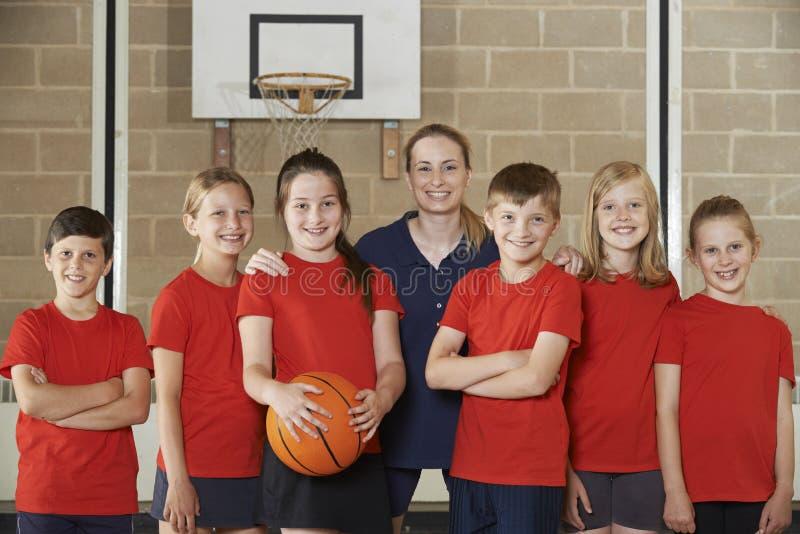 Stående av grundskolabasket Team With Coach fotografering för bildbyråer