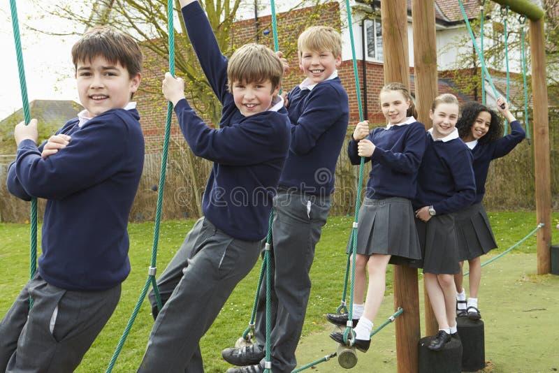 Stående av grundskolaelever på klättringutrustning arkivbilder