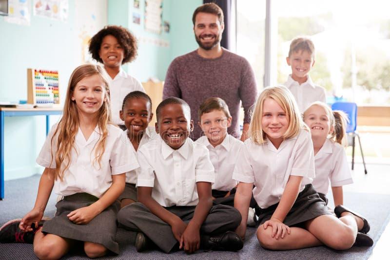 Stående av grundskolaelever som bär enhetligt sammanträde på golv i klassrum med den manliga läraren arkivfoto