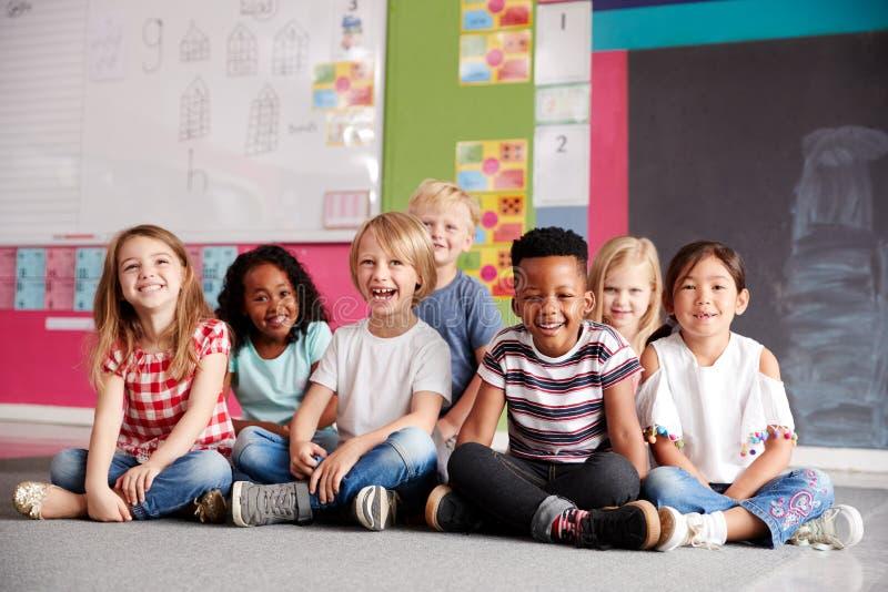 Stående av grundskolaelever som sitter på golv i klassrum royaltyfri foto