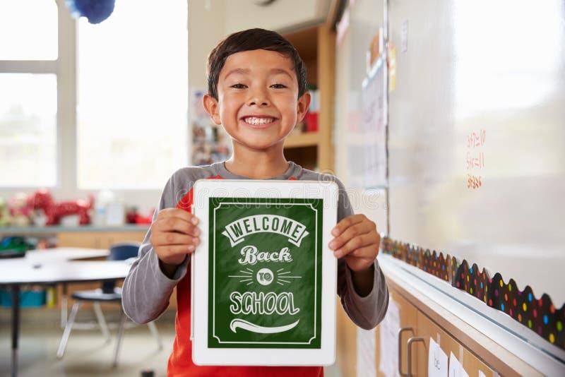 Stående av grundskolaflickan som rymmer en smart minnestavla fotografering för bildbyråer