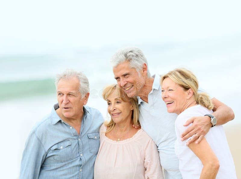 Stående av gruppen av pensionärer på stranden royaltyfria bilder