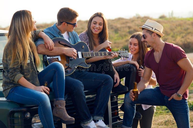 Stående av gruppen av vänner som spelar gitarren och dricker öl arkivfoton