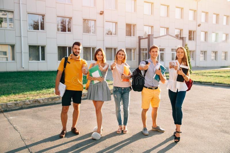 Stående av gruppstudenter i tillfällig dräkt med böcker som visar upp tummar royaltyfria foton
