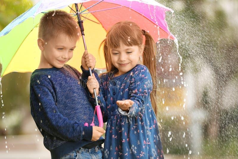 Stående av gulliga barn med paraplyet arkivfoto
