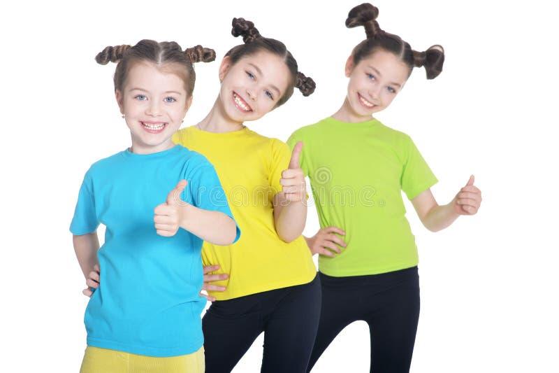 Stående av gulliga små flickor som poserar på vit bakgrund royaltyfri foto