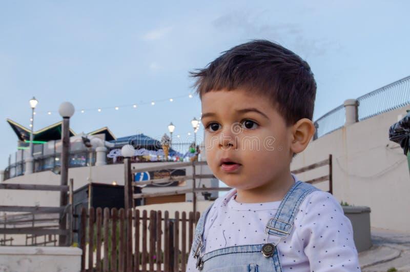 Stående av gulliga två år gammalt pojkemörker att höra royaltyfria bilder