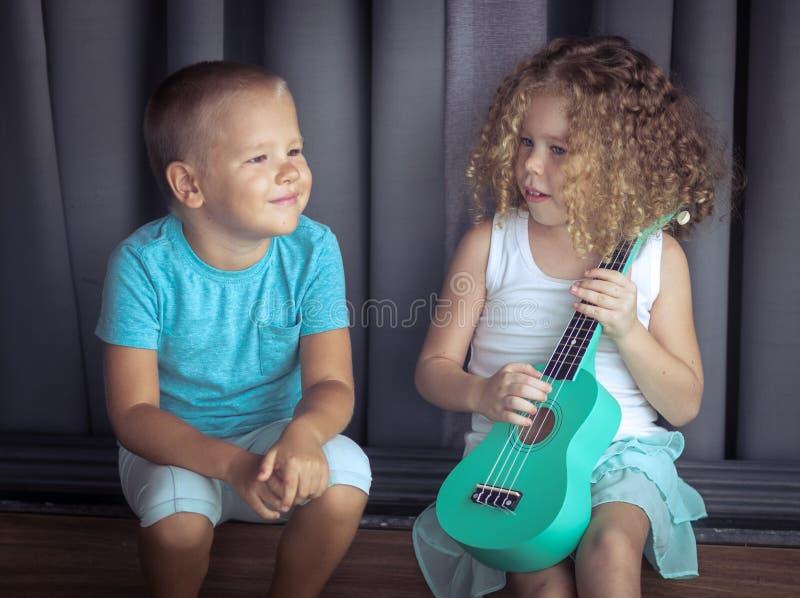 Stående av gulliga ungar med ukulelet royaltyfri fotografi