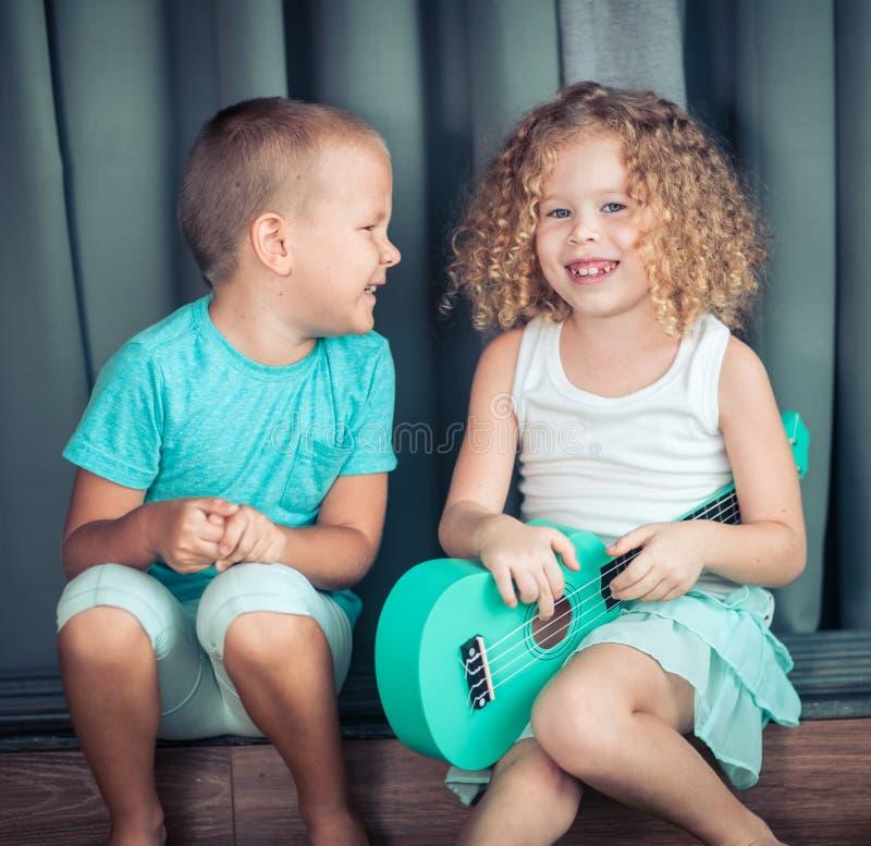Stående av gulliga ungar med ukulelet royaltyfria foton