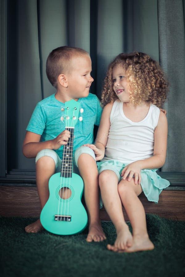 Stående av gulliga ungar med ukulelet royaltyfri bild