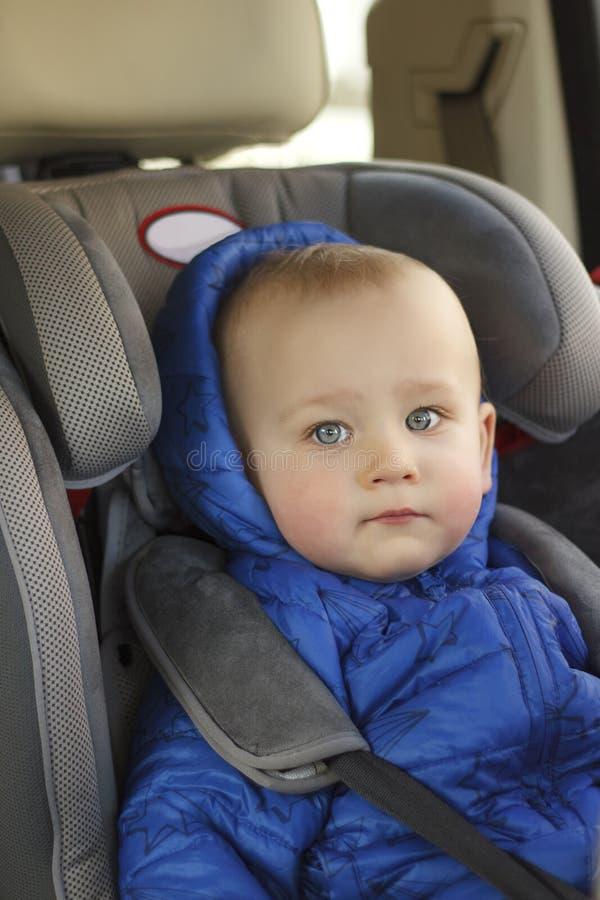 Stående av gulligt litet barnpojkesammanträde i bilsäte Barntrans.säkerhet arkivbilder