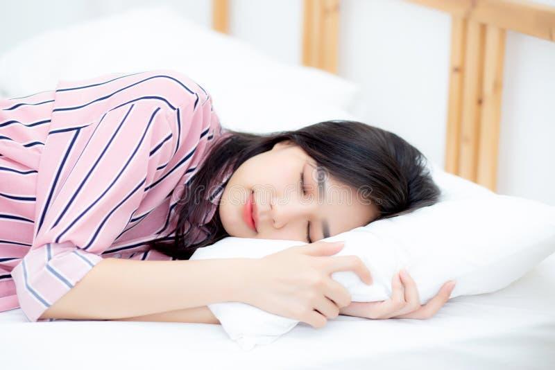 Stående av härlig asiatisk sömn för ung kvinna som ligger i säng med huvudet på kudden som är bekväm och som är lycklig med friti royaltyfri bild