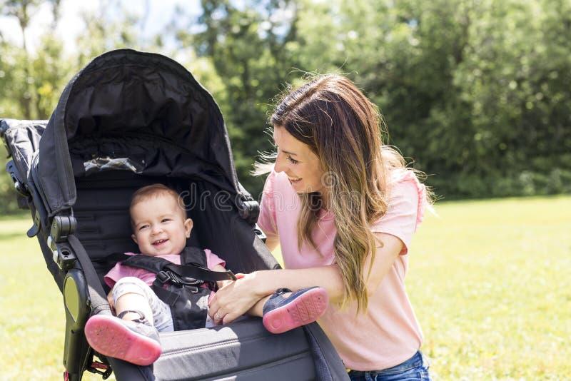 Stående av härlig driftig barnvagn för ung kvinna i parkera arkivbild