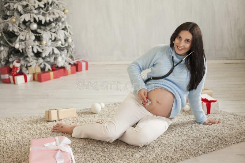 Stående av härlig ferie för gåva för träd för nytt år för gravid kvinnajul royaltyfri bild