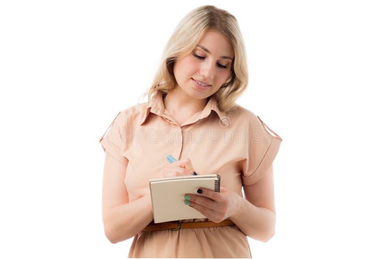Stående av härlig ung blond kvinnahandstil på en notepad, isolerad vit bakgrund royaltyfri fotografi