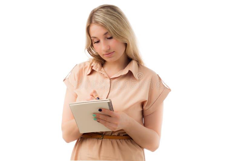 Stående av härlig ung blond kvinnahandstil på en notepad, isolerad vit bakgrund arkivfoto