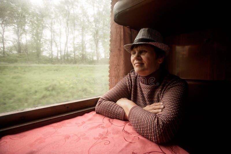 Stående av härliga 60 år gammal kvinna i hatten som sitter i drev royaltyfri bild