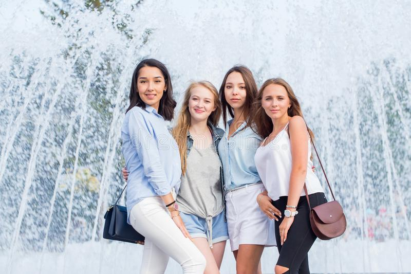Stående av härliga fyra kvinnor nära springbrunnen i staden Lyckliga flickor har gyckel som poserar och ser kameran arkivbild