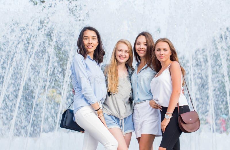 Stående av härliga fyra kvinnor nära springbrunnen i staden Lyckliga flickor har roligt posera royaltyfria foton