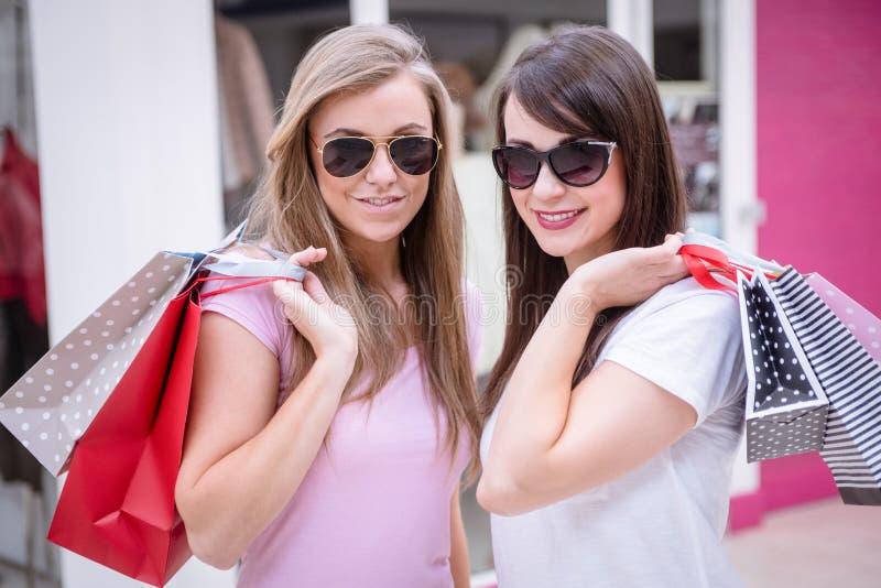 Stående av härliga kvinnor i solglasögon som rymmer shoppingpåsar royaltyfria foton