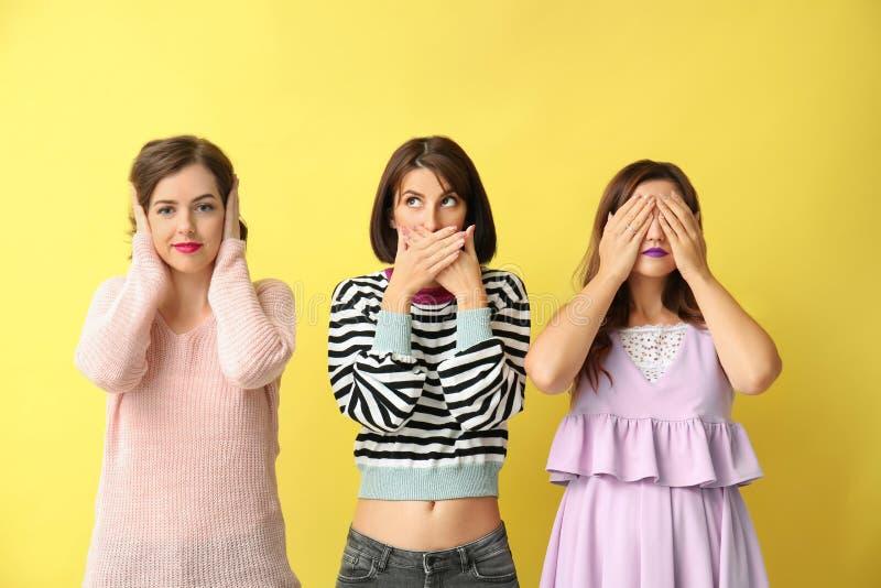 Stående av härliga kvinnor som hör ingen ondska, ser ingen ondska och talar ingen ondska, på färgbakgrund royaltyfria bilder