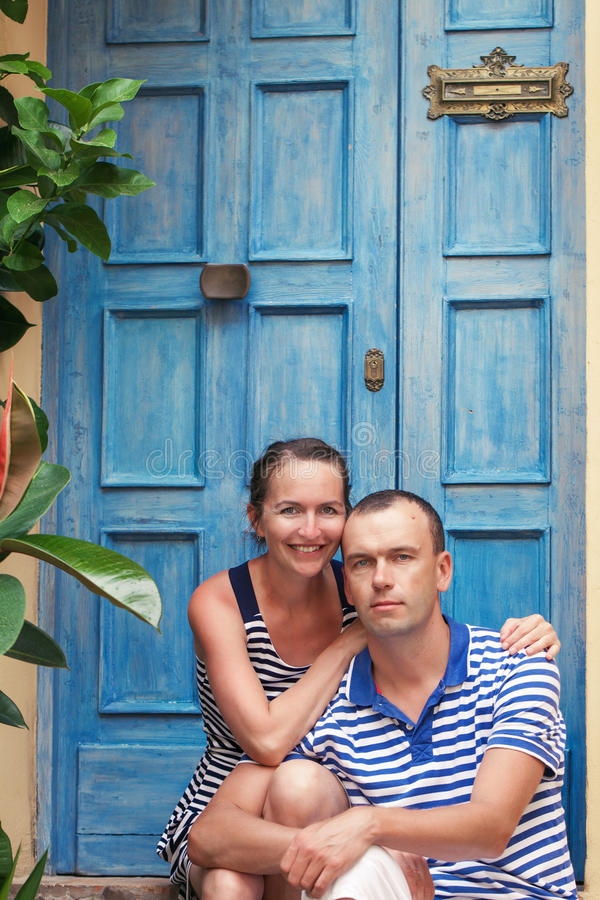 Stående av härliga och lyckliga par på bakgrund av den blåa dörren arkivfoton