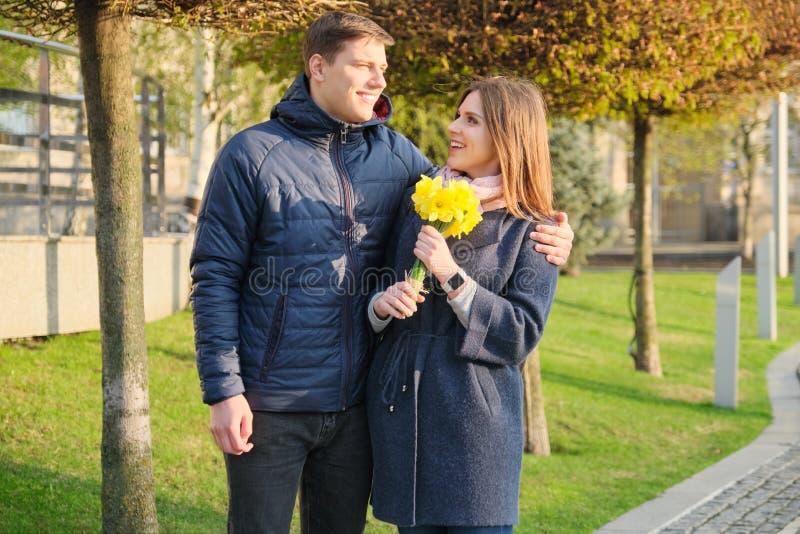 Stående av härliga par i staden, den lyckliga unga mannen och kvinnan som omfamnar, guld- timme royaltyfri foto