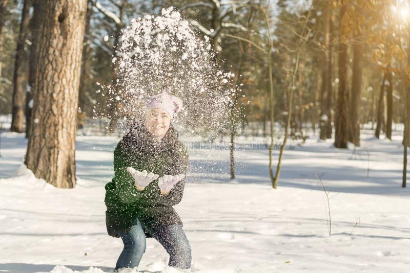 Stående av härligt kasta för flicka som är insnöat vintern Den lyckliga unga kvinnan spelar med en insnöad solig vinterdag En fli royaltyfria bilder