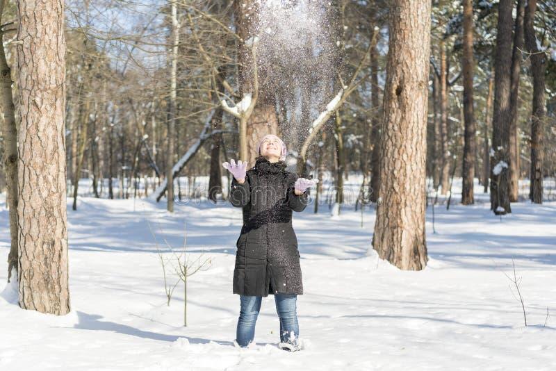 Stående av härligt kasta för flicka som är insnöat vintern Den lyckliga unga kvinnan spelar med en insnöad solig vinterdag En fli royaltyfria foton