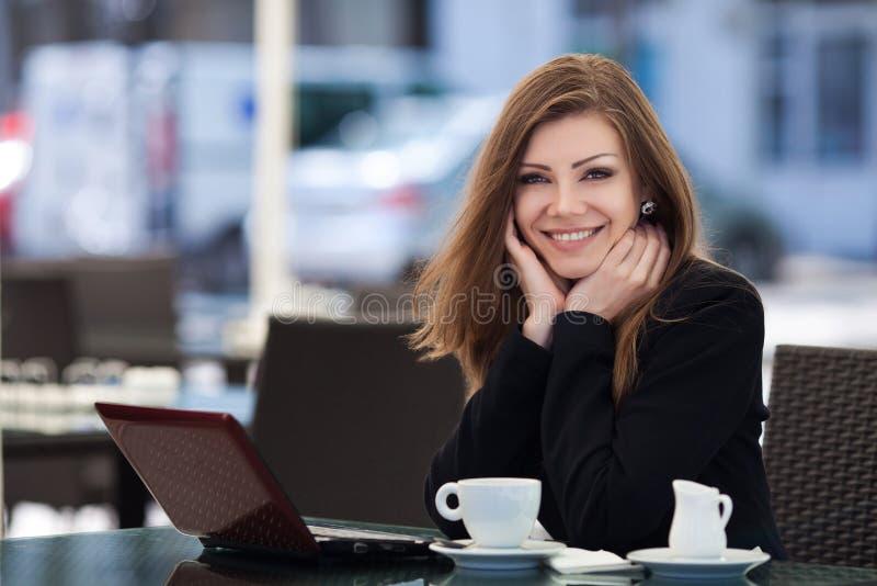 Stående av härligt le kvinnasammanträde i ett kafé med den utomhus- bärbara datorn arkivfoto