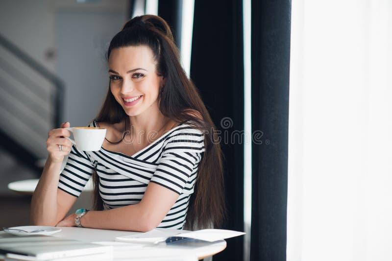 Stående av härligt sammanträde för ung kvinna på en tabell med en kopp kaffe i handen som ser kameran som ler medan på royaltyfri bild